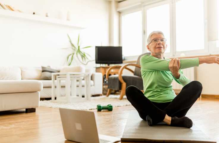 An aging woman stretching indoors; Getty Images