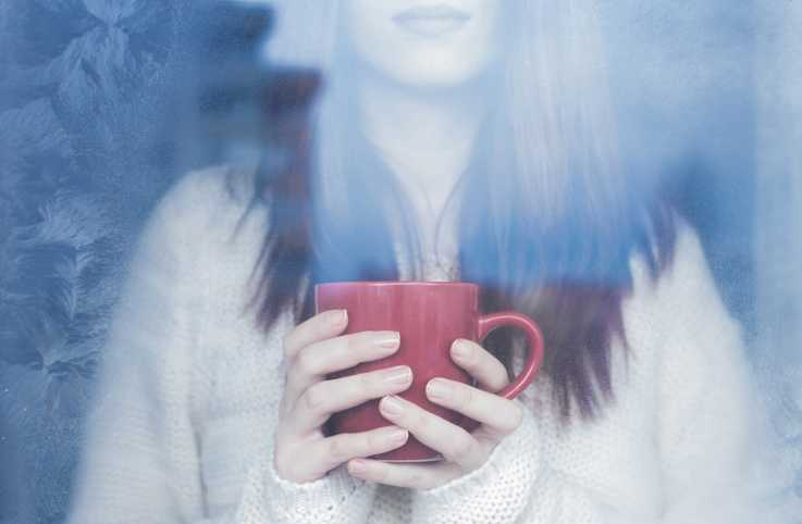 A woman, mug in hand, gazes out a window on a wintry day