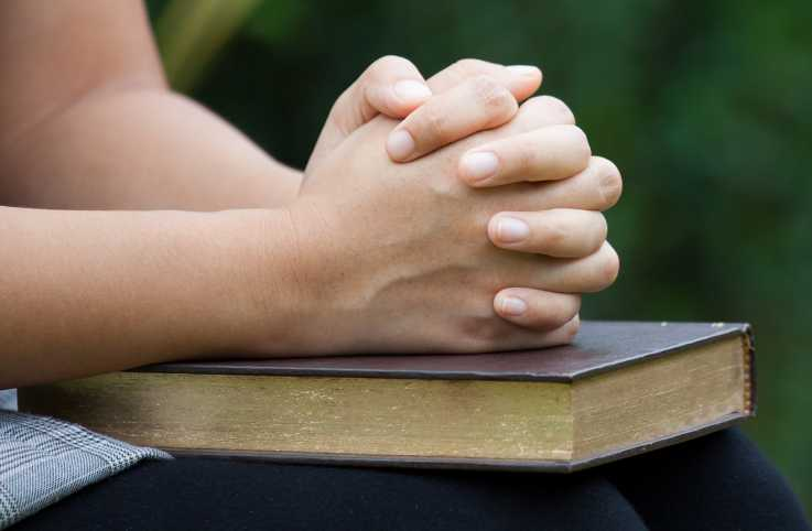 A woman's praying hands rest on an Bible