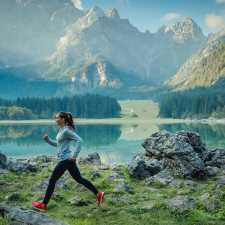 A woman jogger run with mountains in the background