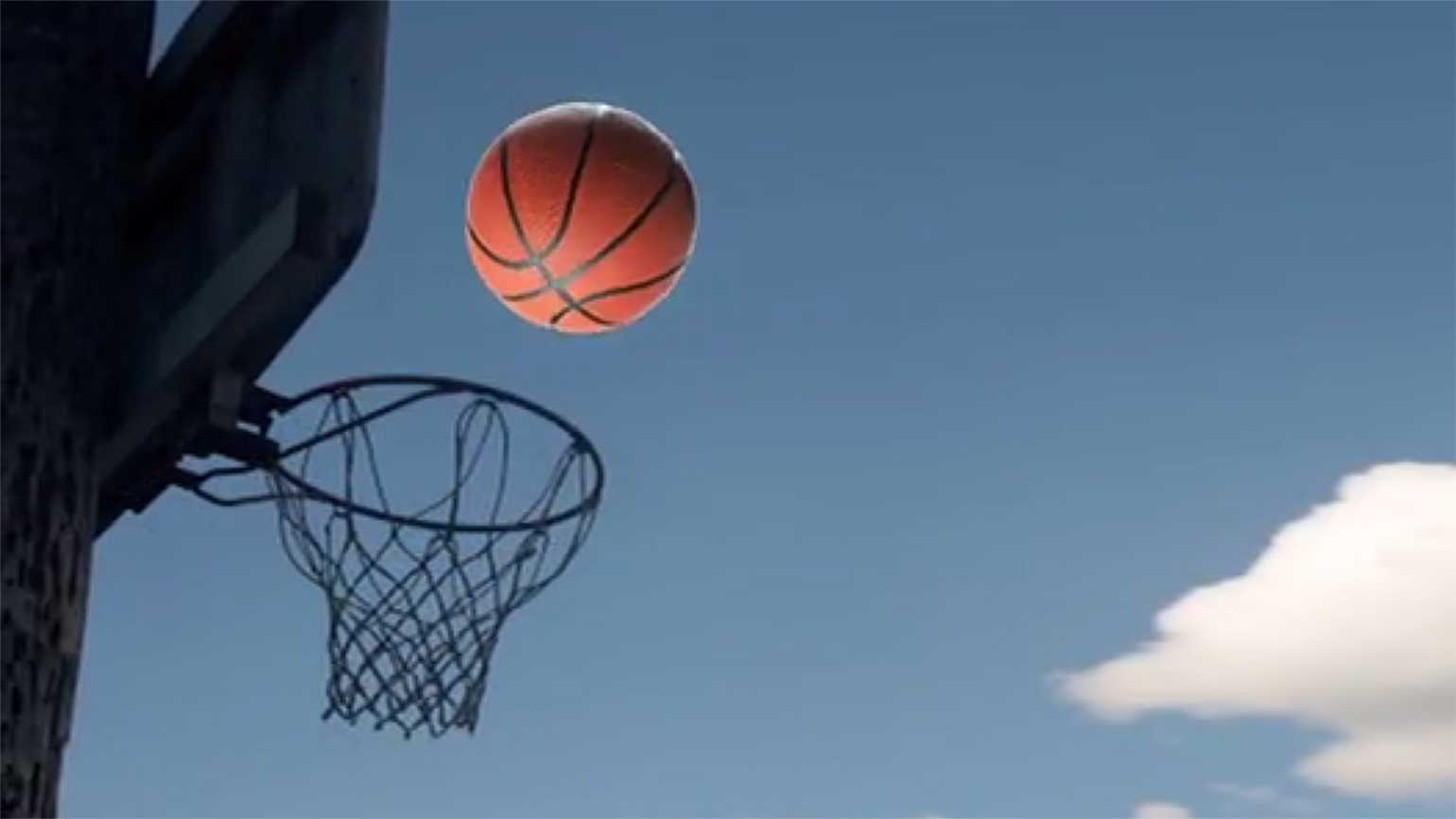 A basketball in midflight approaches the hoop and backboard