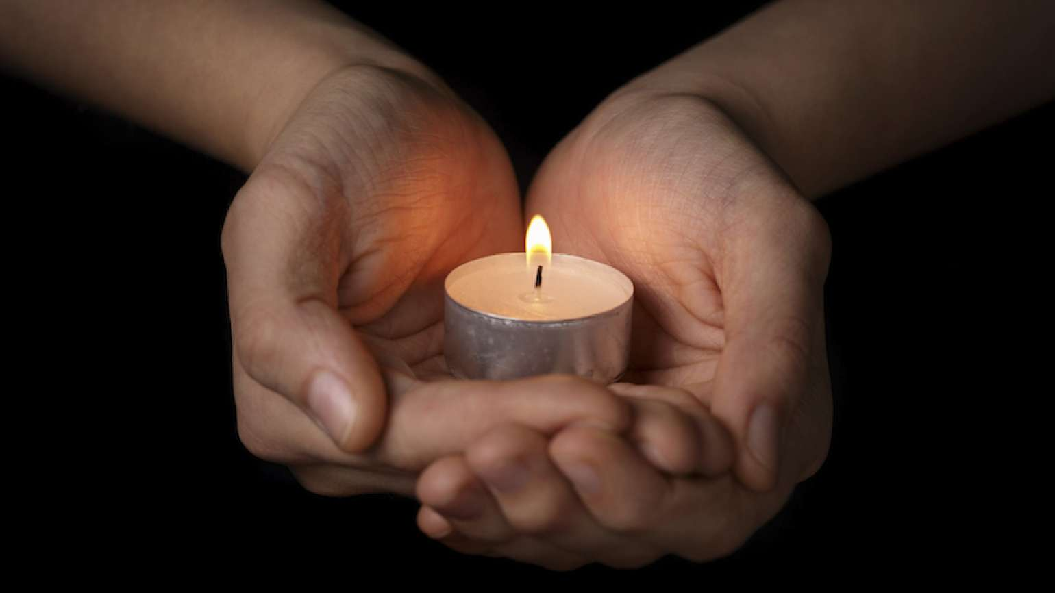 Woman's hands cupping a candle. Photo by Goo Dween123, Thinkstock.