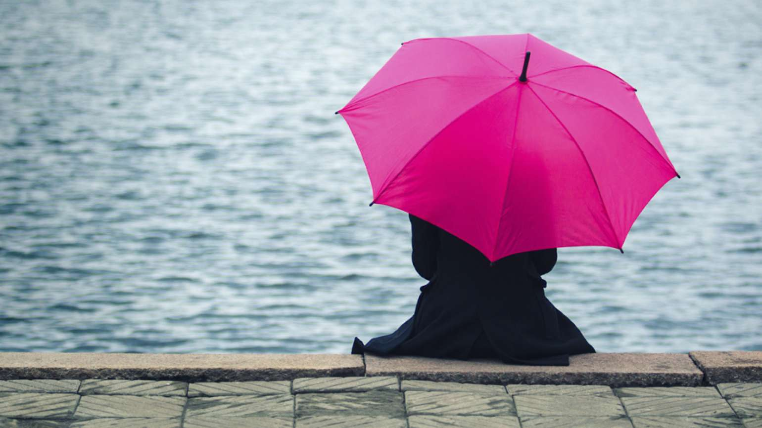 A woman sits at a river's edge holding a pink umbrella preparing for a storm. Prepare for the storms of life with these tips