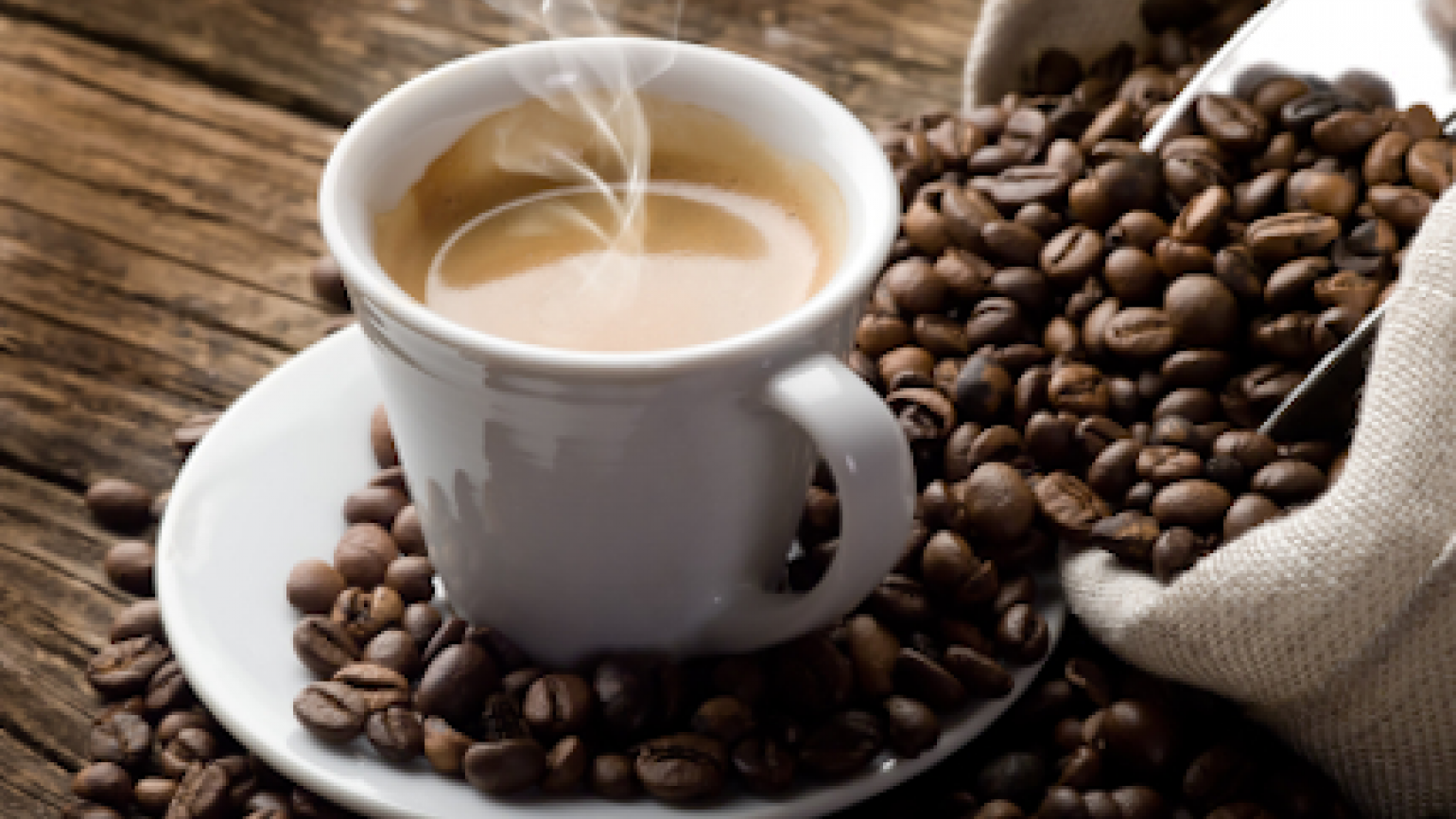 A steaming cup of coffee surrounded by coffee beans