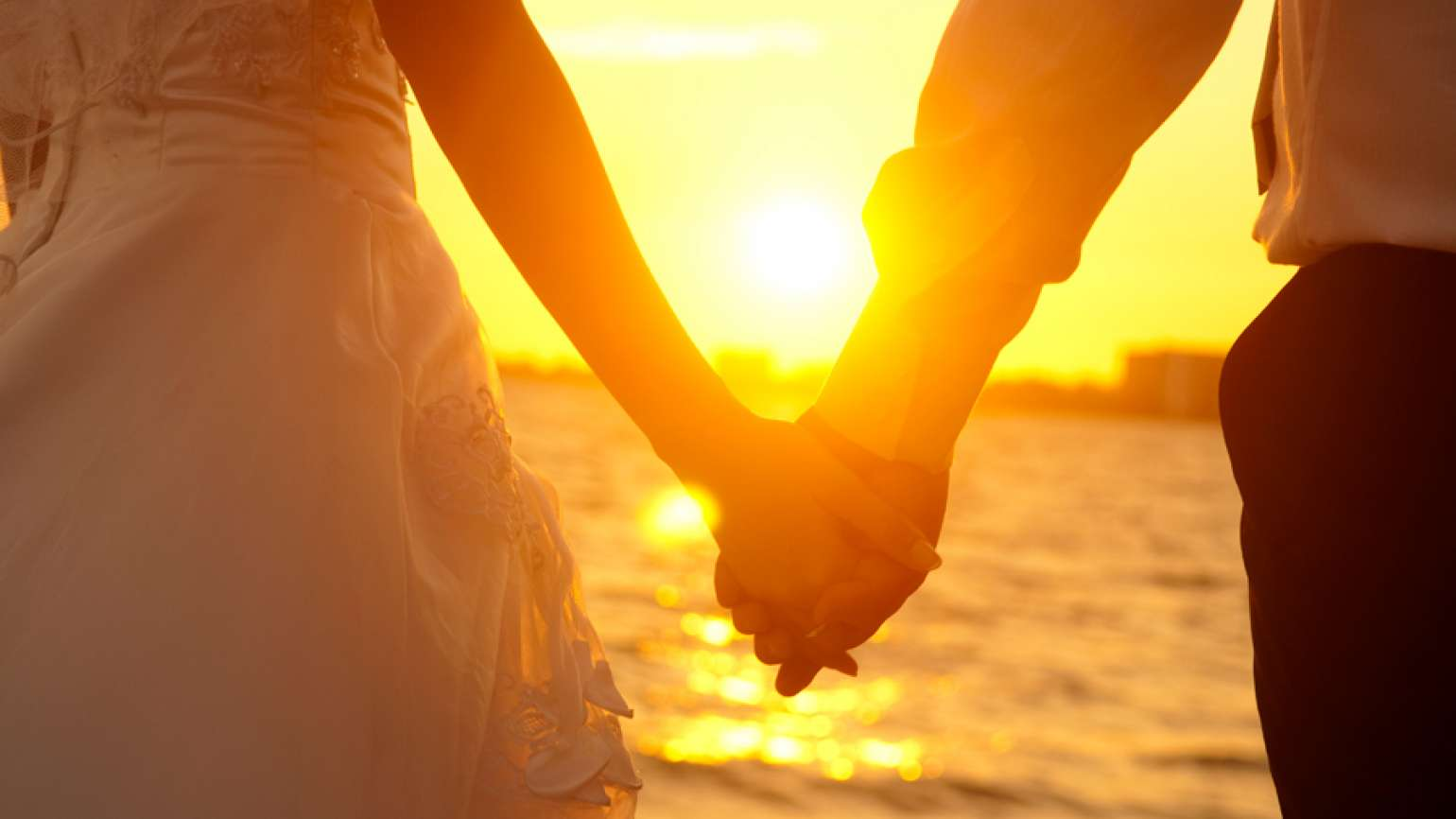 Newlyweds hold hands on a sun-splashed beach.