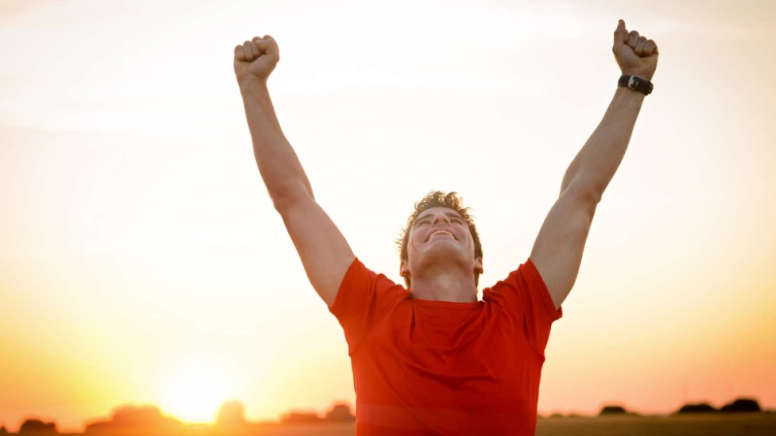 Man with arms lifted in triumph