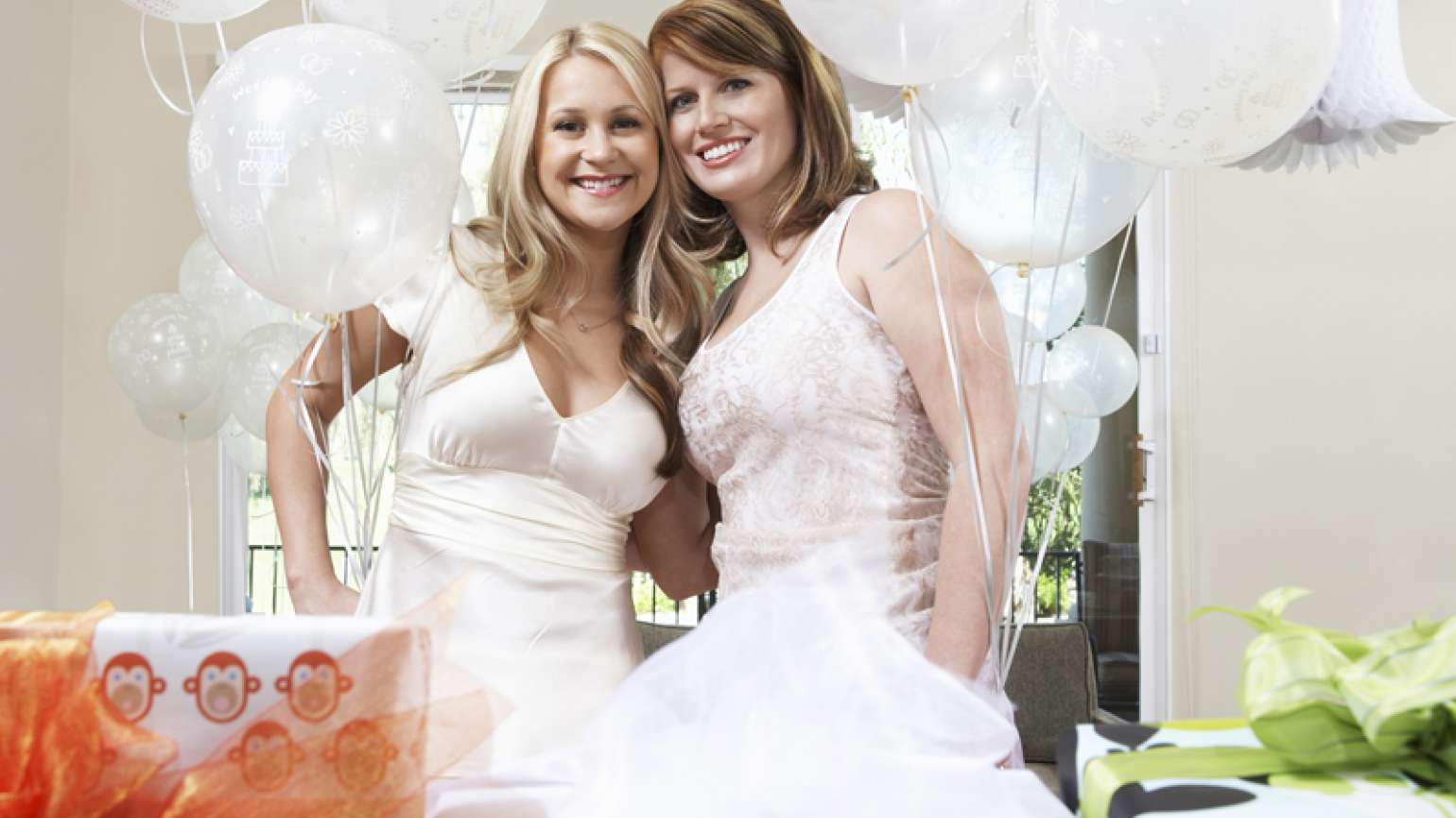 Two smiling women pose for a photo at a bridal shower.