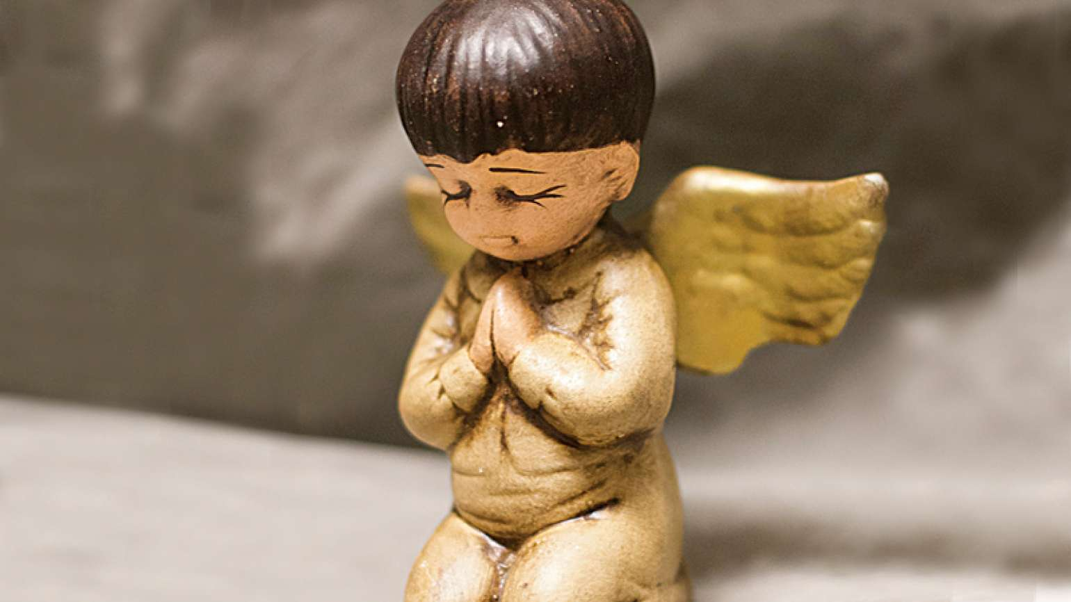 A ceramic angel with mocha-colored skin and cropped brown hair