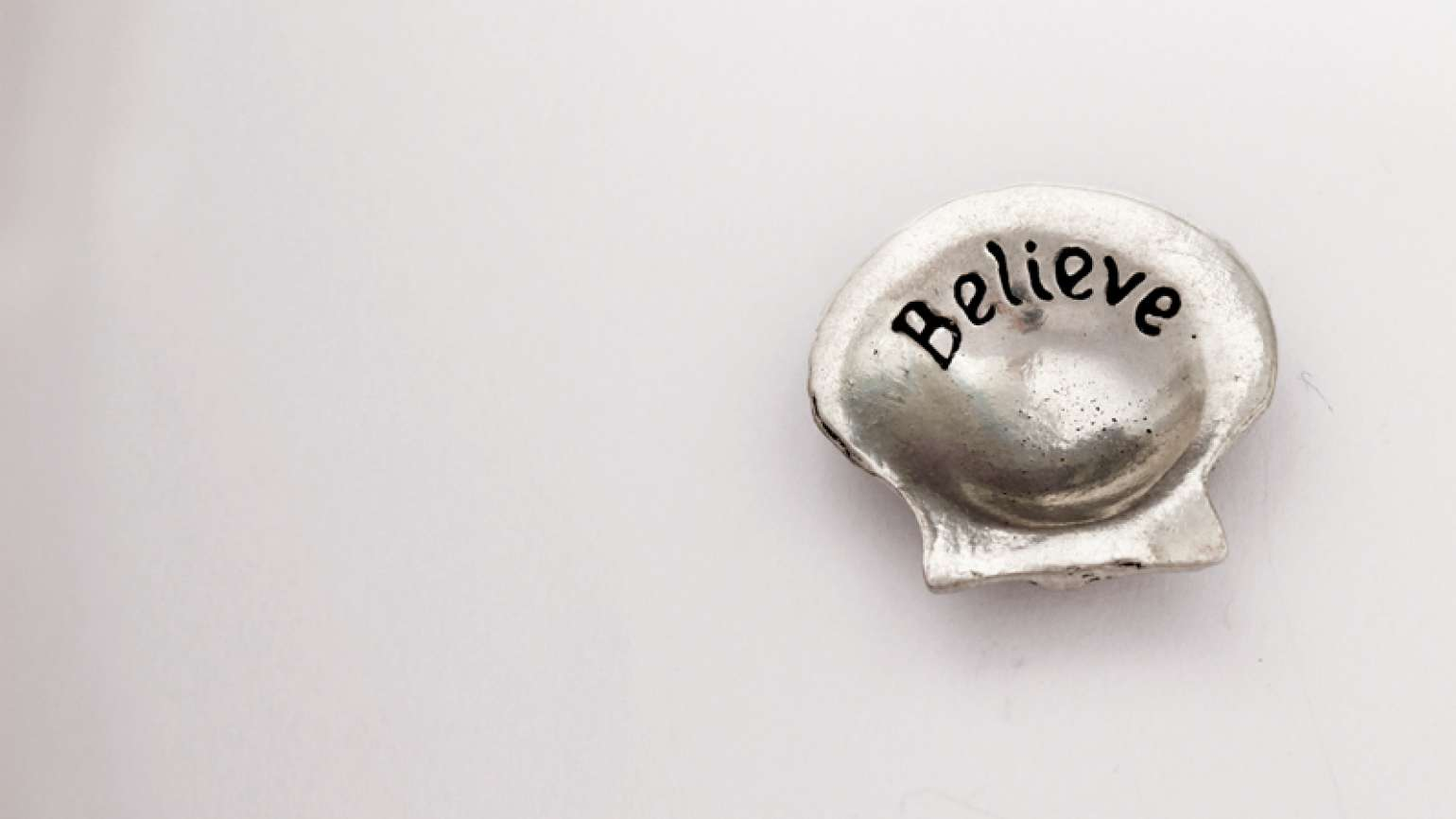 The word 'believe' inscribed on a seashell
