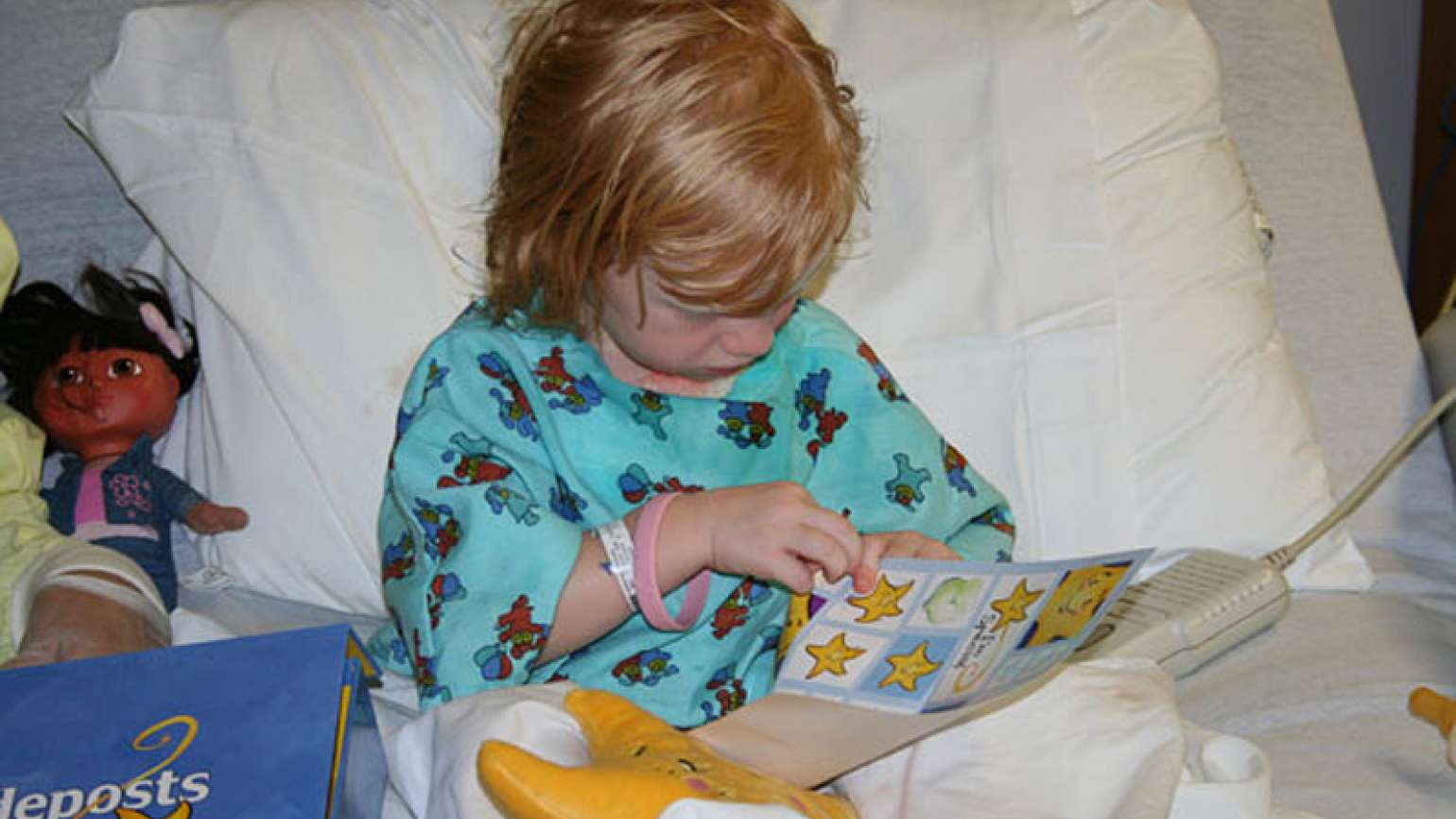 A sick child plays with her Comfort Kit from Guideposts Outreach