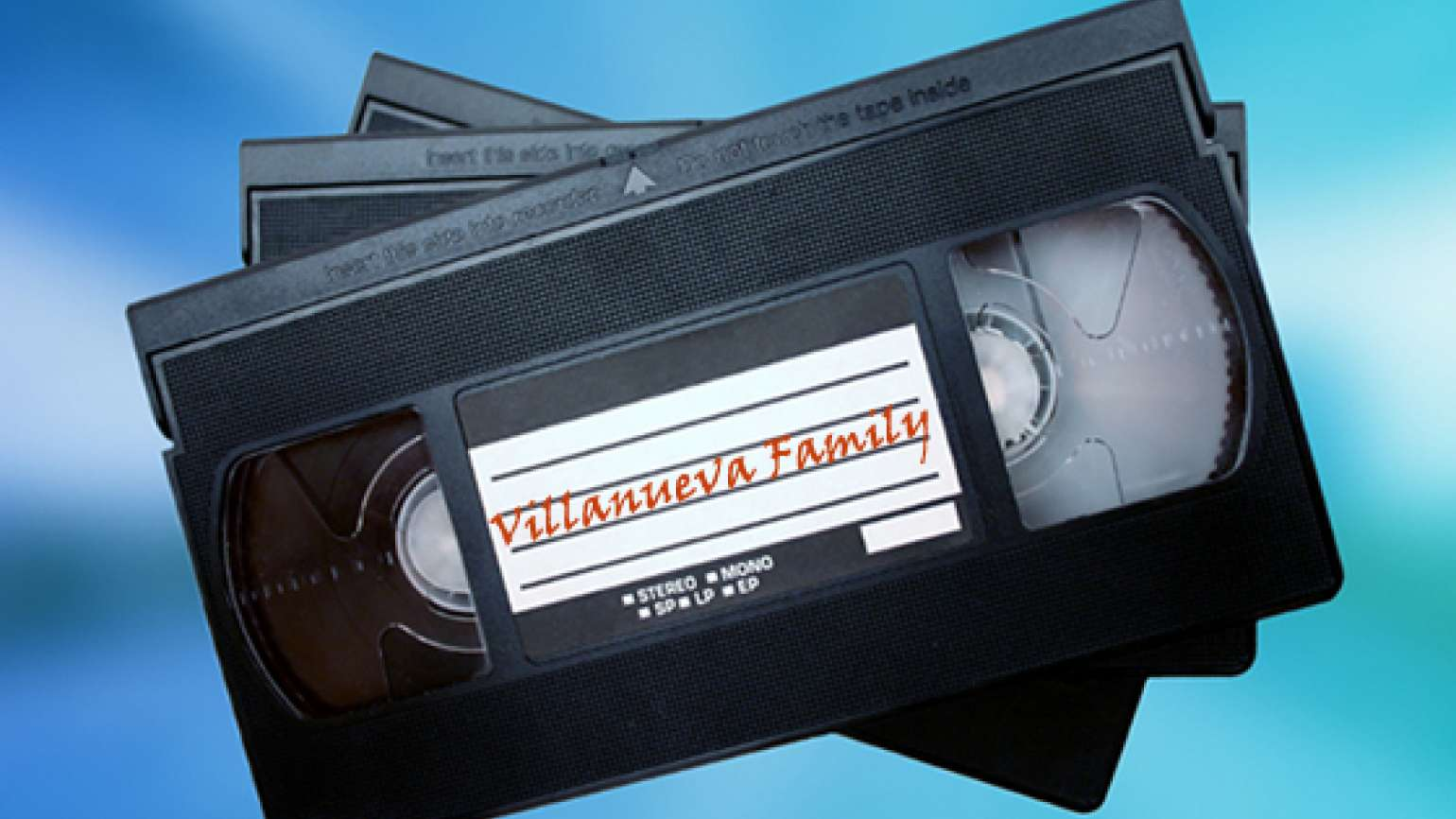 "A stack of video tapes, the top of which is labeled ""Villanueva Family."""