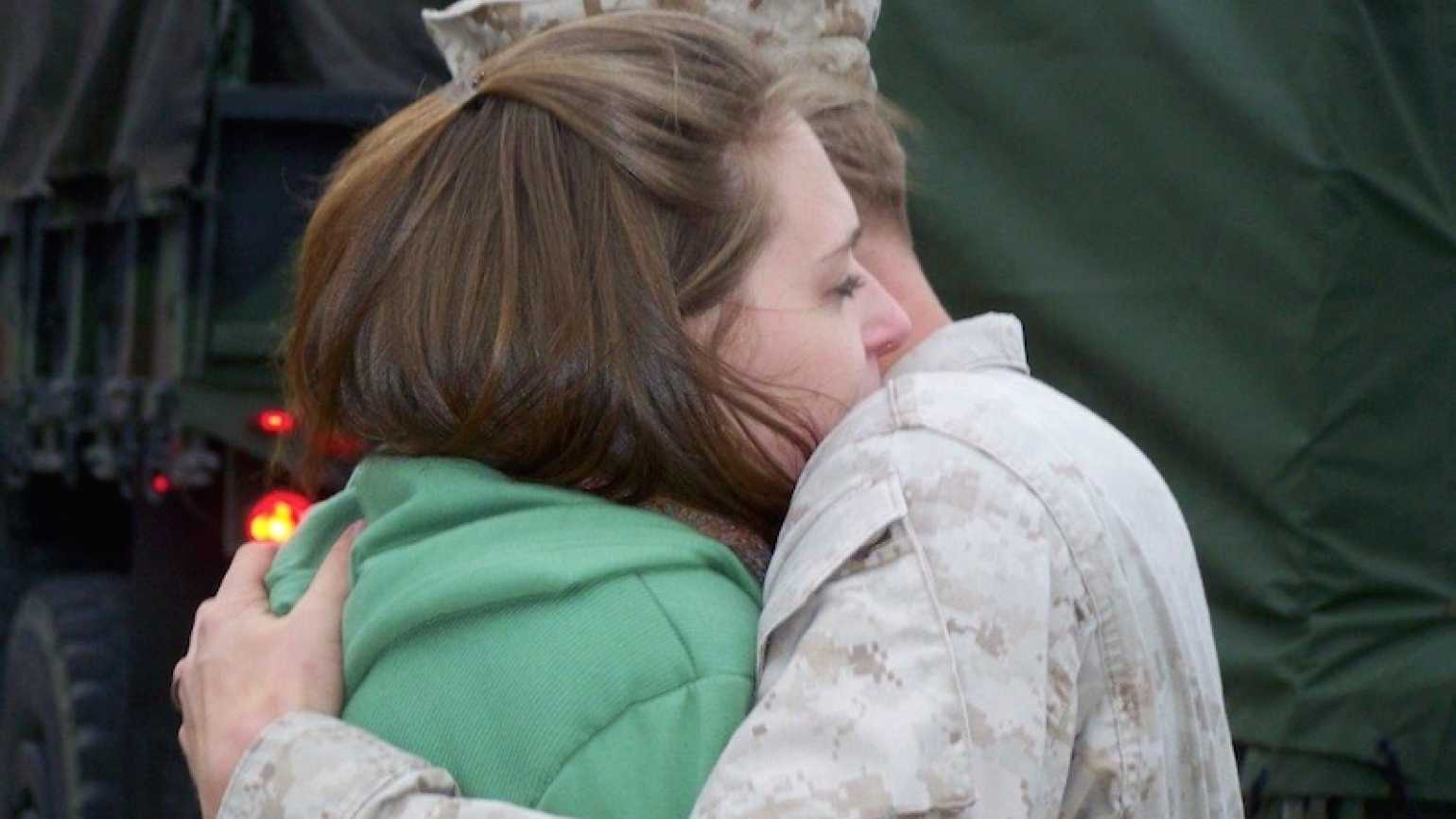 Edie's Marine Corps son hugging his wife before he's deployed