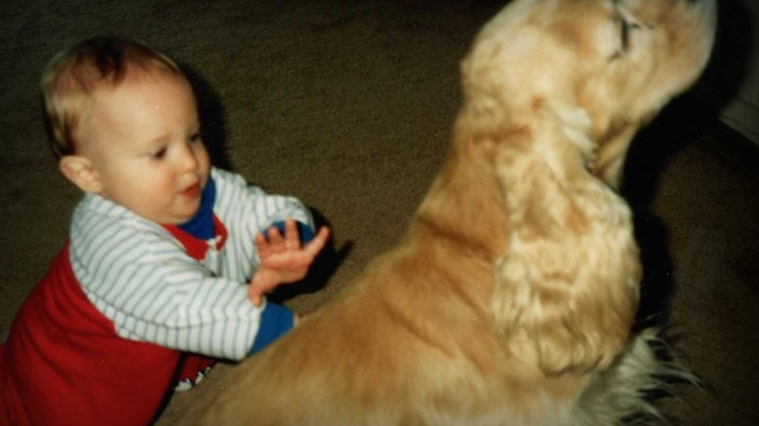 Jimmy as a toddler learning to walk with the family dog, Sherlock.