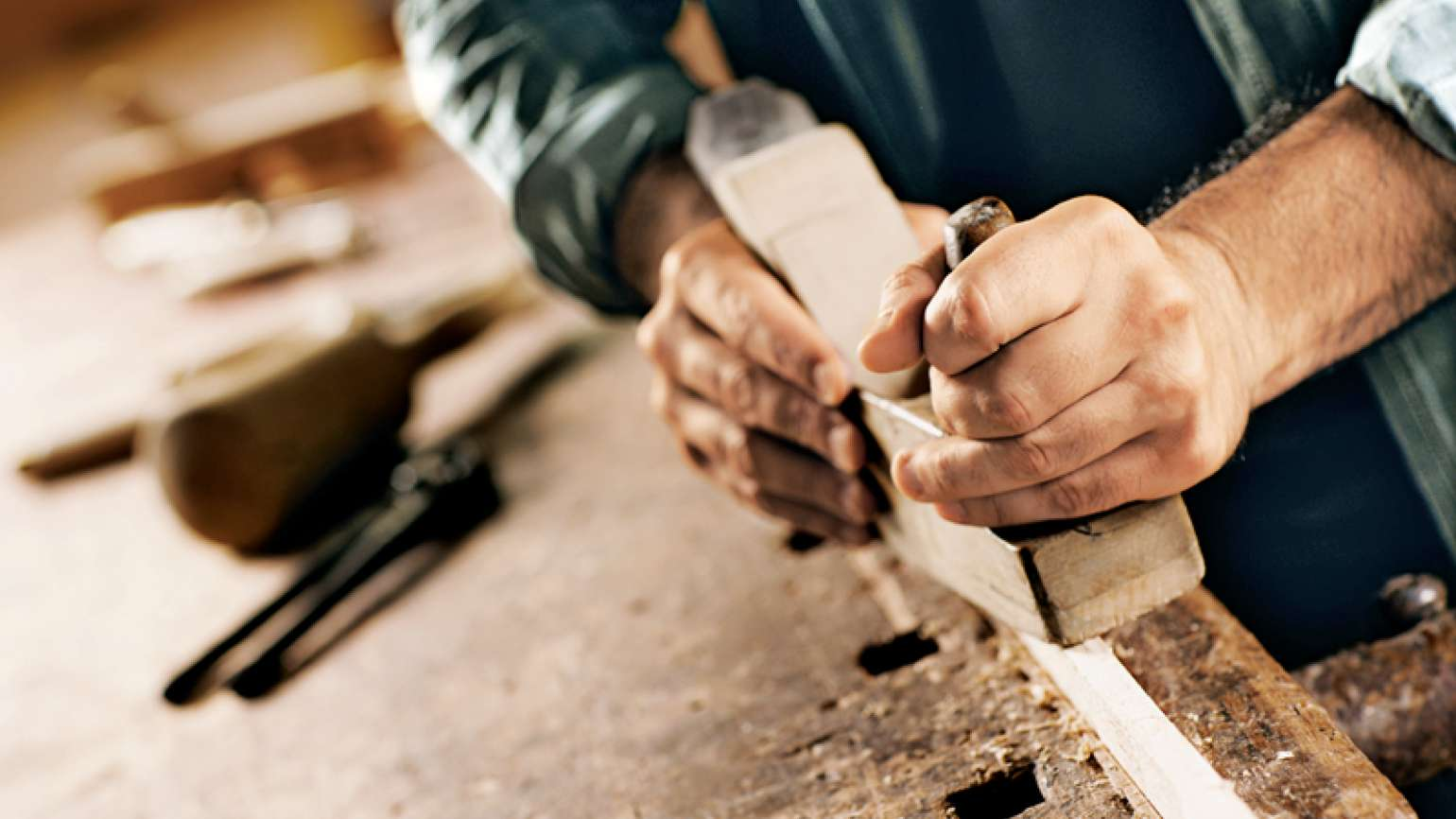 A man's hands working with wood on a workbench