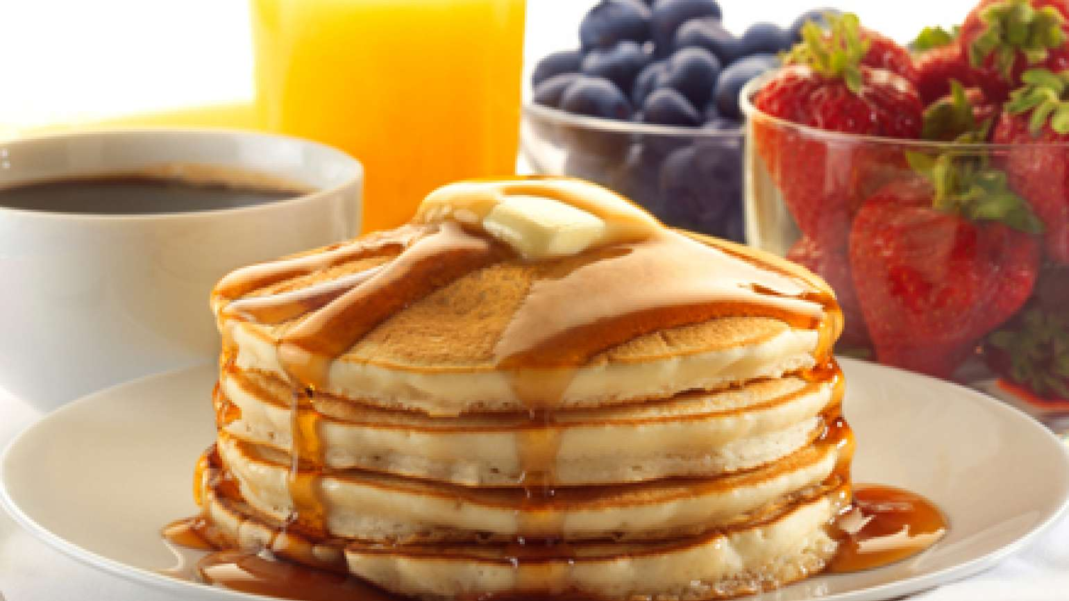 A stack of pancakes covered in butter and syrup