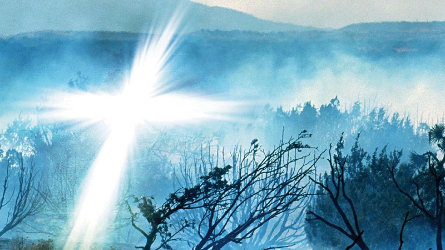 A glowing white cross appears in a smoky, fire-ravaged landscape.