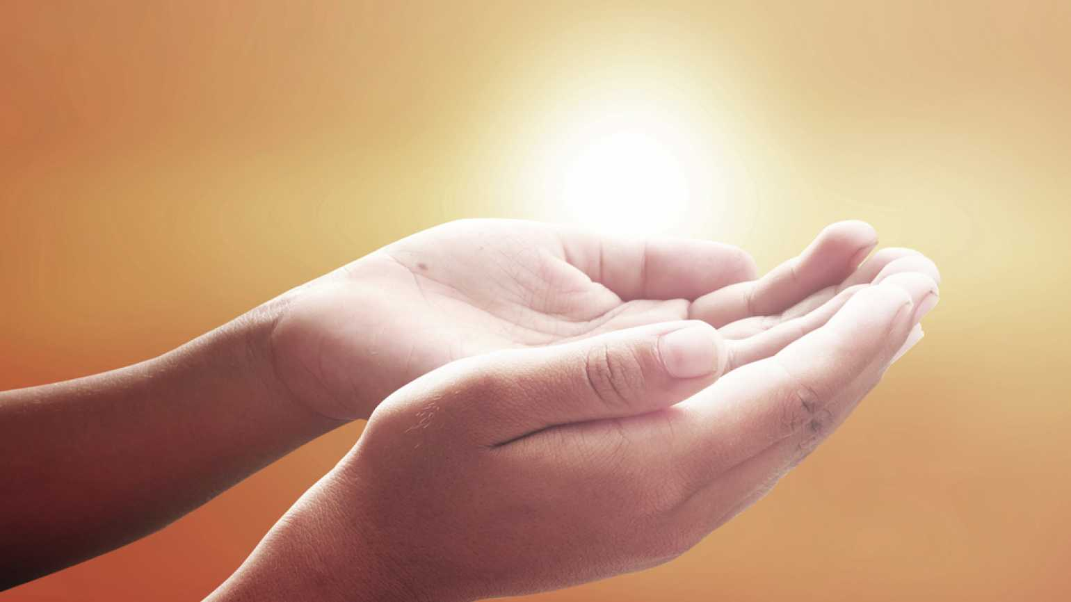 hands positioned in prayer in front of a sunrise