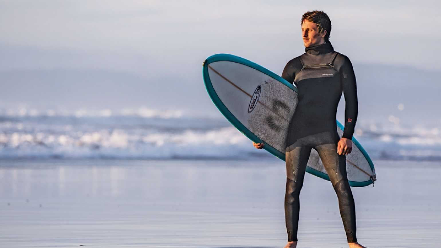 Scott Stephens stands on the beach, surfboard under his arm.