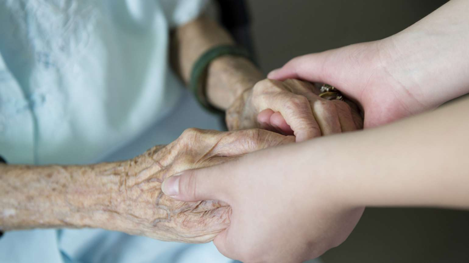 An elderly woman's hands are clasped lovingly by a younger woman's hands.
