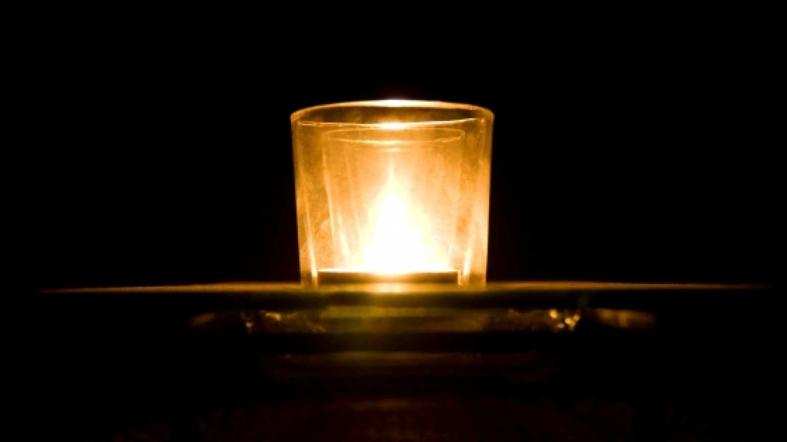 a single, lit votive candle