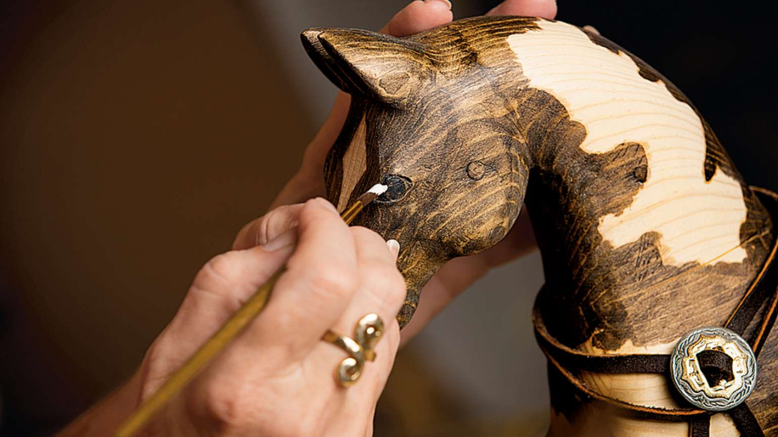 Jackie works meticulously in her studio on one of her equine creations.