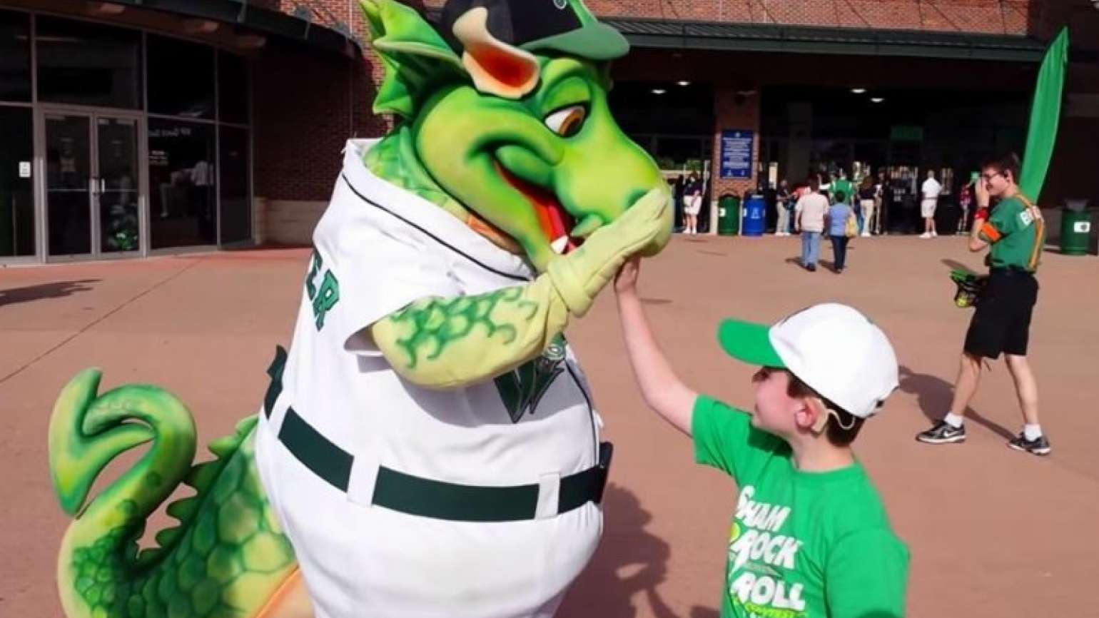 Hunter enthusiastically high fives Heater, the Dragons mascot