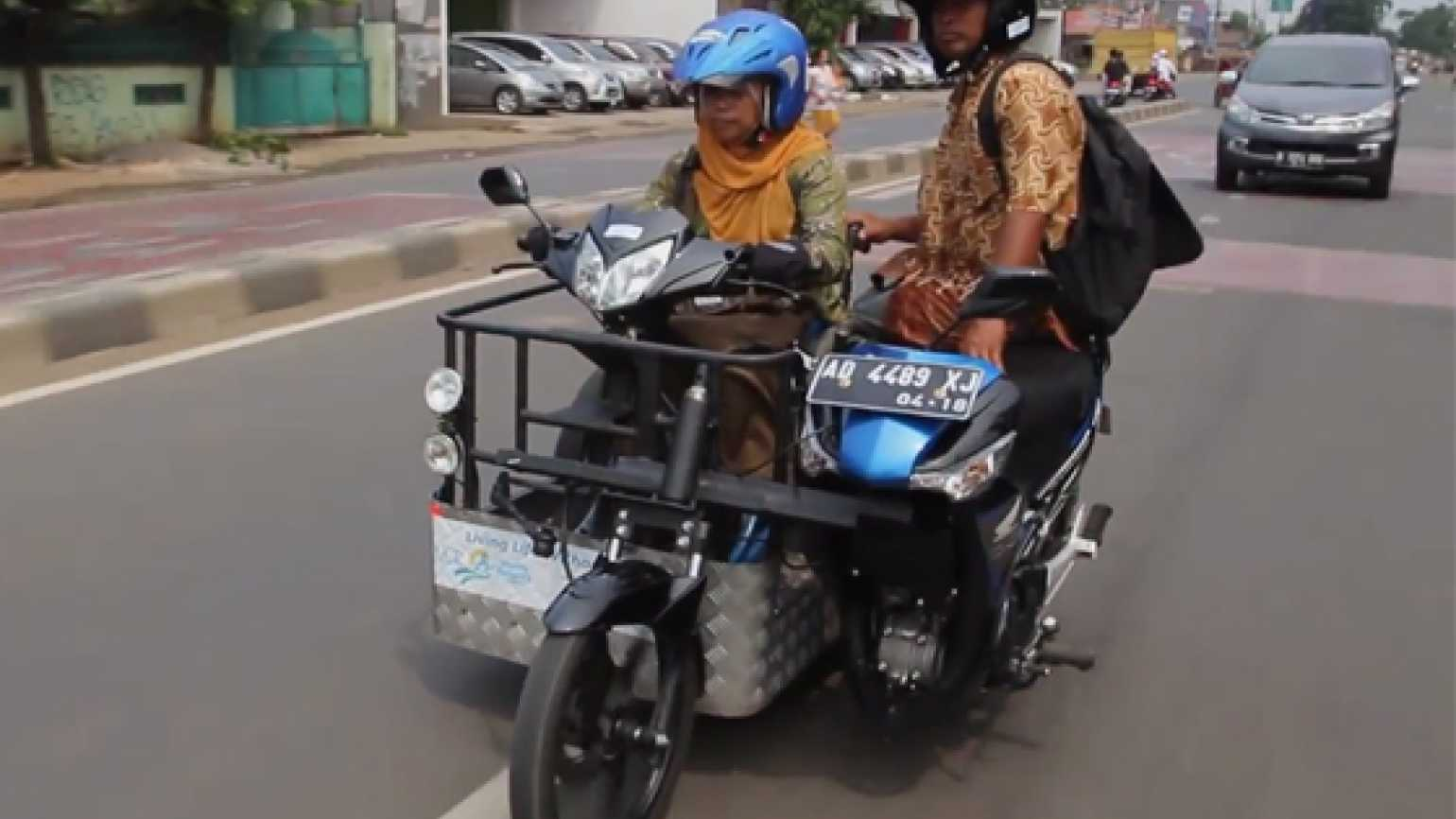 Paraplegic Sri Lestari and her brother ride in a specially designed motorcycle.