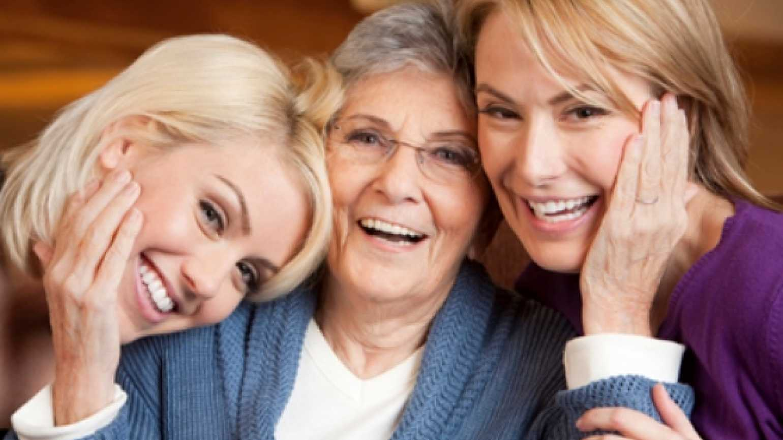 An older mother surrounded by two daughters