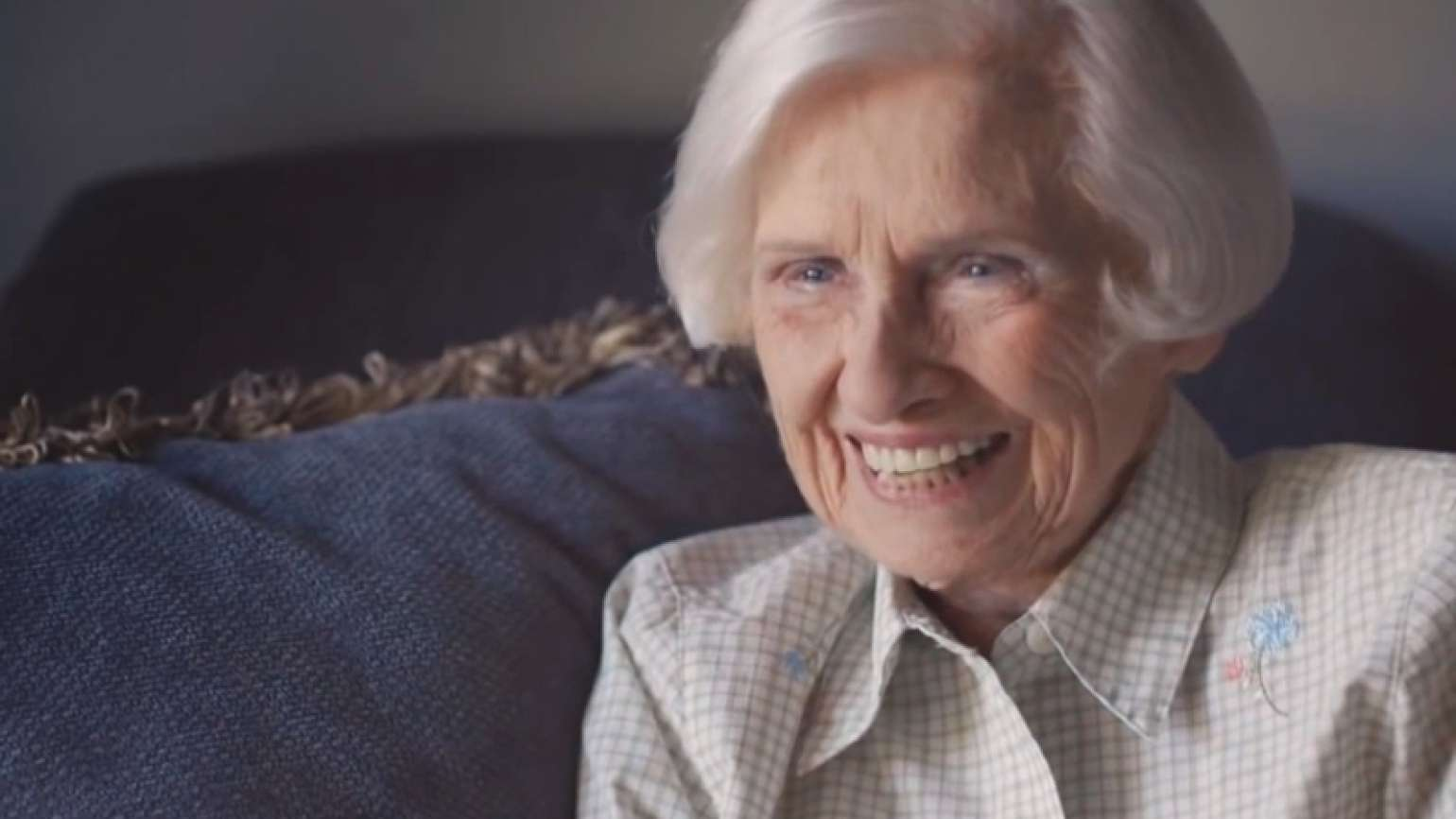 Old woman laughing on couch