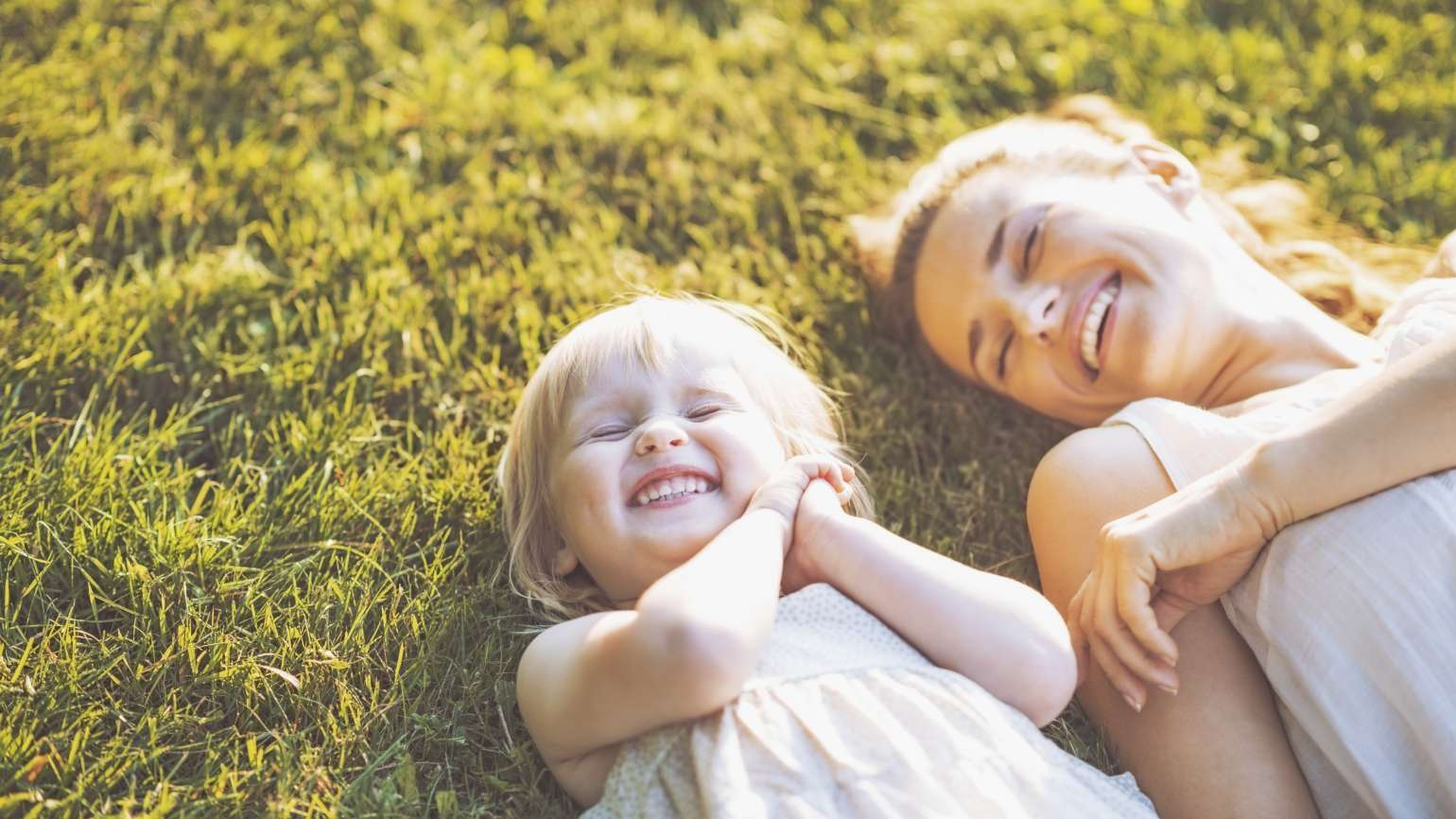 Mom and daughter laying in grass, smiling -- Thinkstock