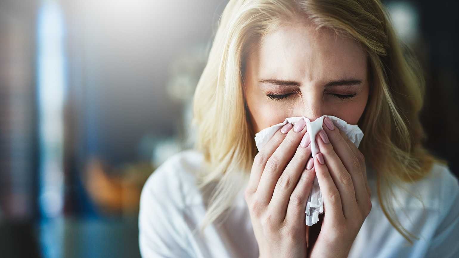 A woman suffering with allergies sneezes