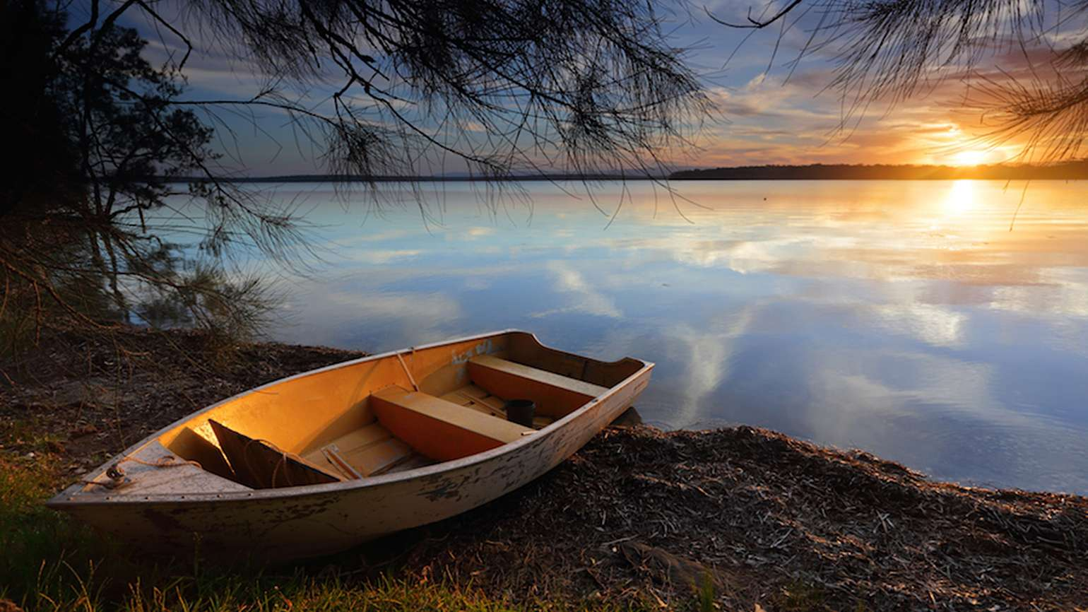 A boat on a lake at sunset