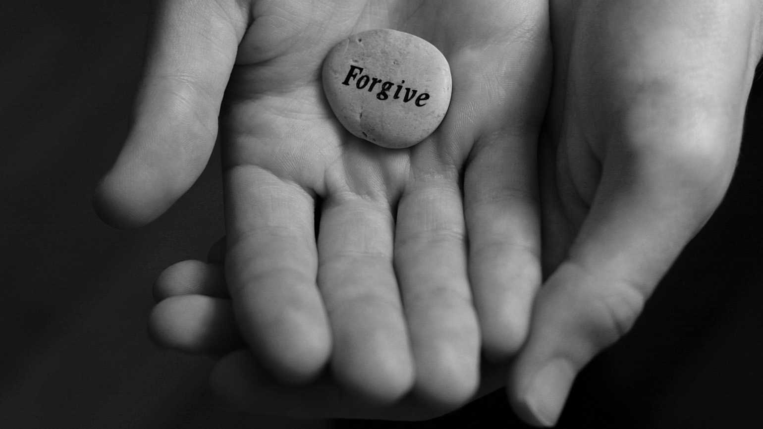 A black and white photo of hands holding a stone with 'Forgive' engraved on it.