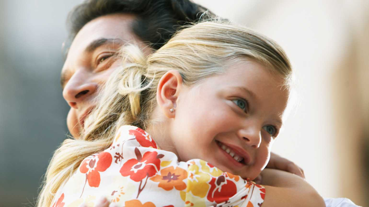 A young girl lovingly embraces her father, her face beaming.