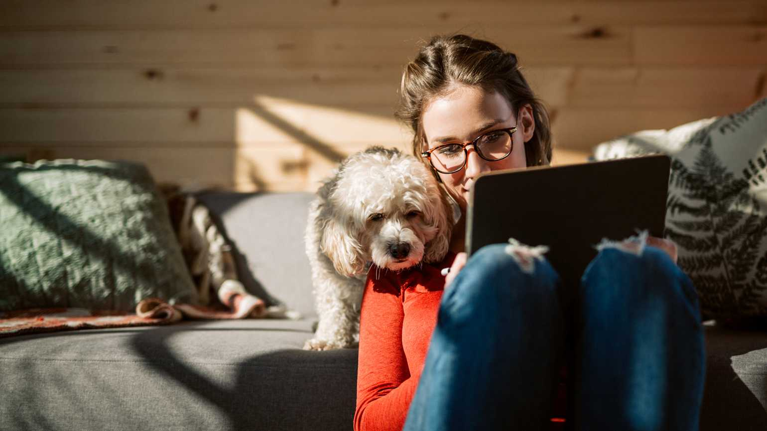 A woman working from home with her dog peering over her shoulder.