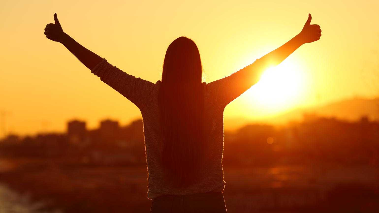 Backlight of a woman raising arms with a thumbs up.