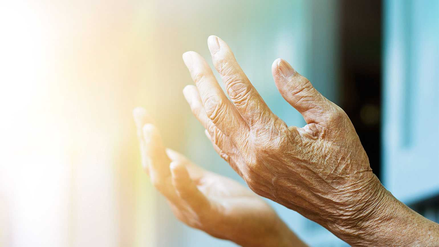 Elderly woman holding her hands out towards light