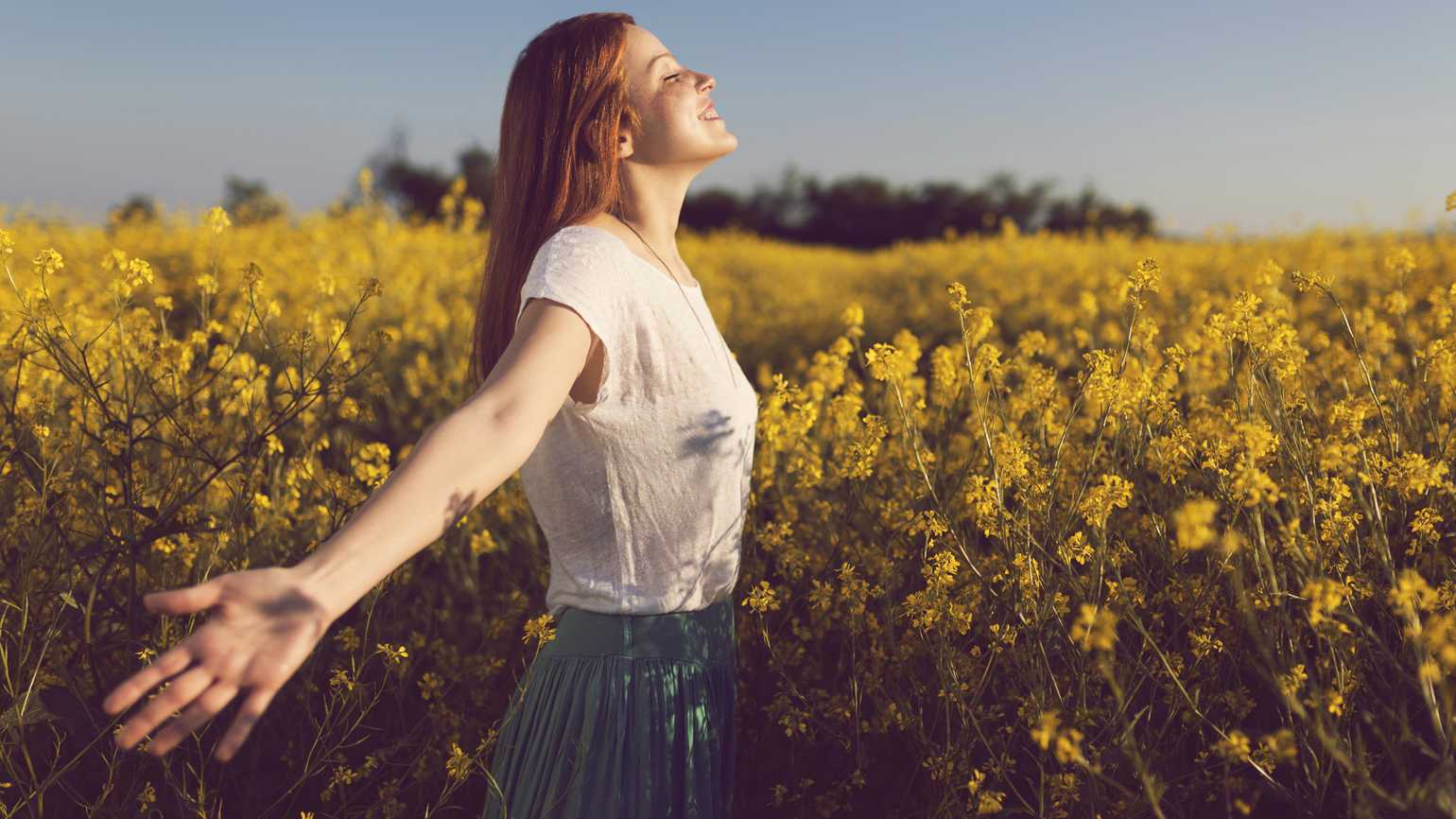 A woman with arms outstretched in a field of yellow flowers.