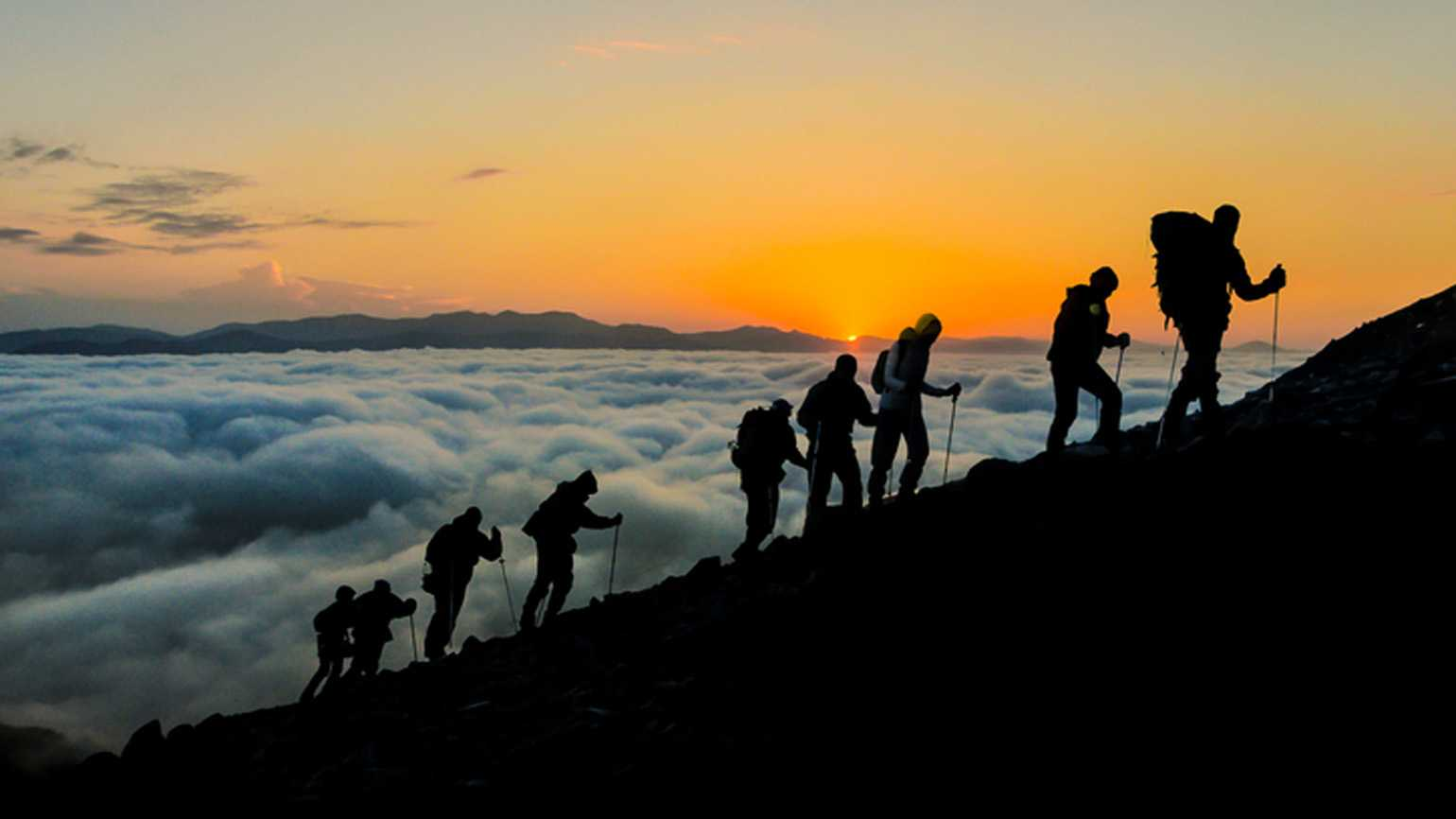 Group of strong hikers walking up a mountain