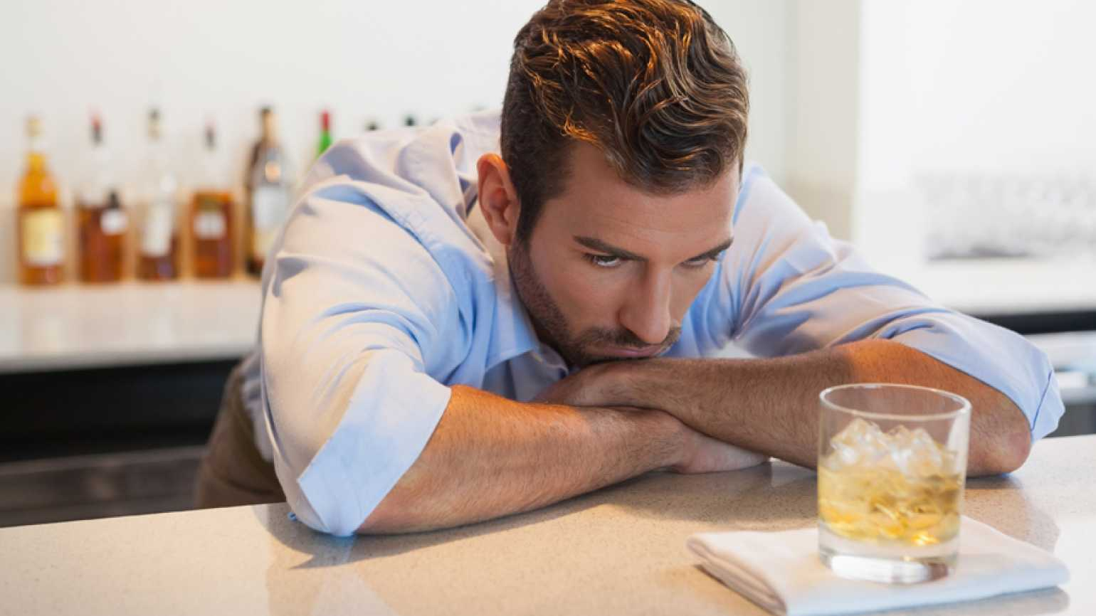A man struggles to resist drinking a glass of alcohol that rests in front of him