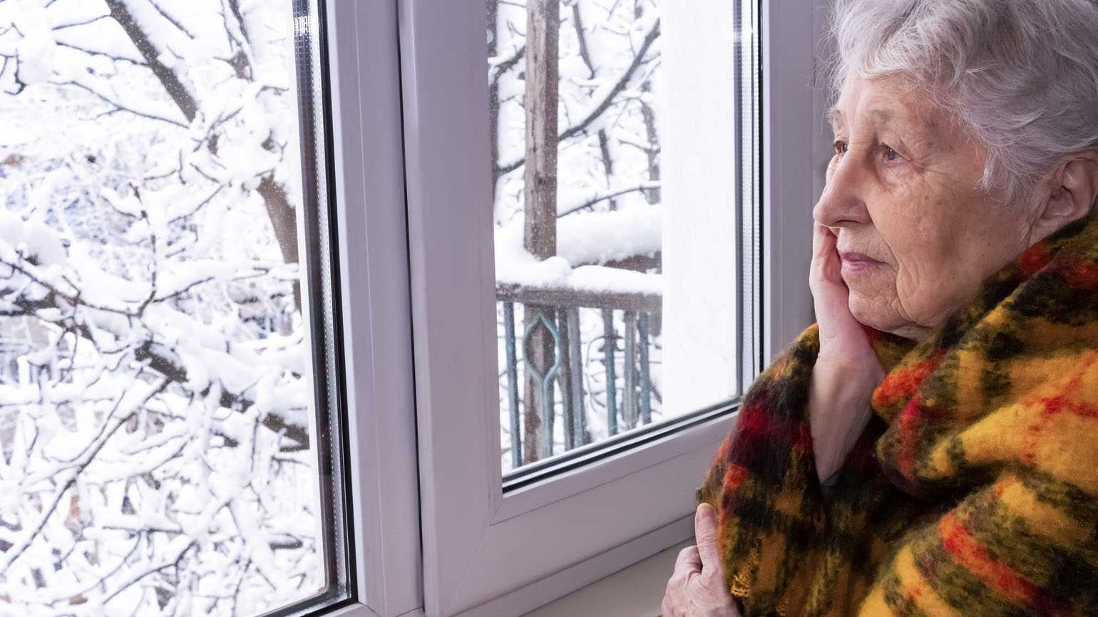 A senior woman looking out of her window; Getty Images