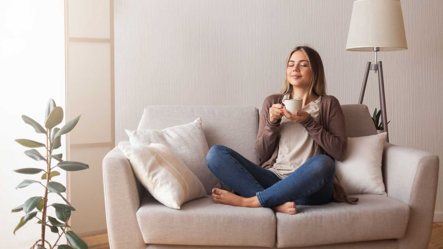 A woman finding peace on her couch; Getty Images