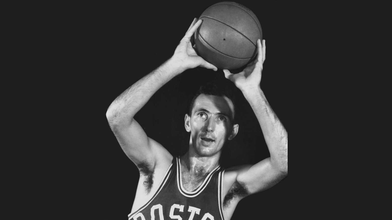 A black and white photo of Bob Cousy in action.