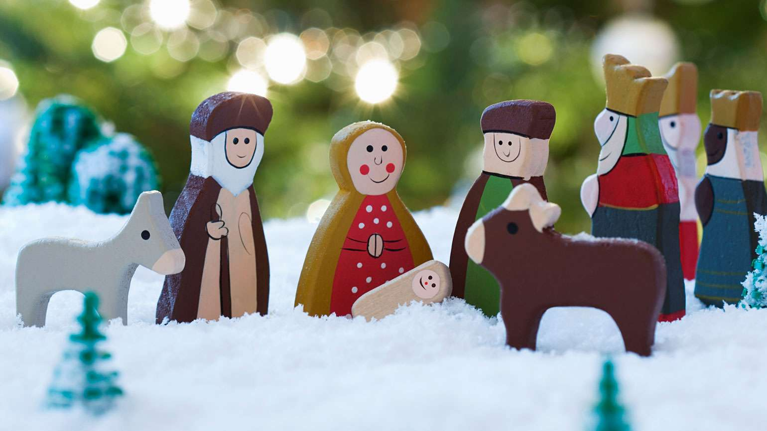 A wooden nativity set, with a colorful Christmas tree behind it