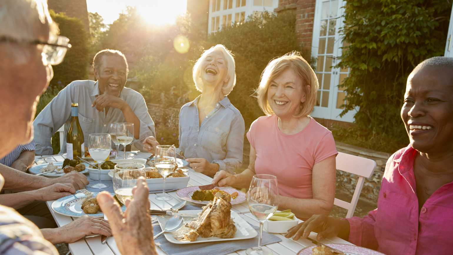 Group of friends laughing around a dinner table