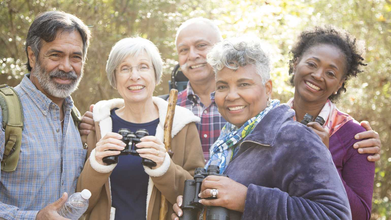 A group of diverse senior friends hiking in the woods.
