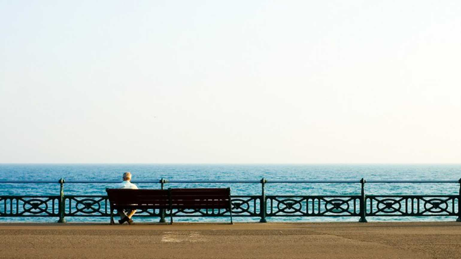 A lonely senior sitting on a bench gazing out to the sea on the beach.