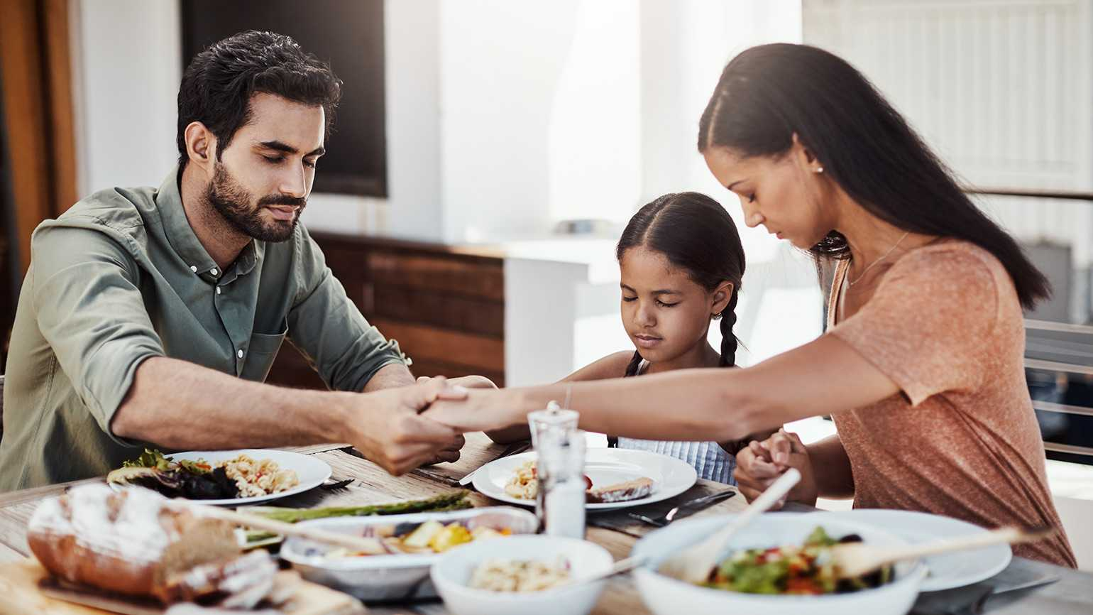 A family holds hands around the dinner table while saying grace