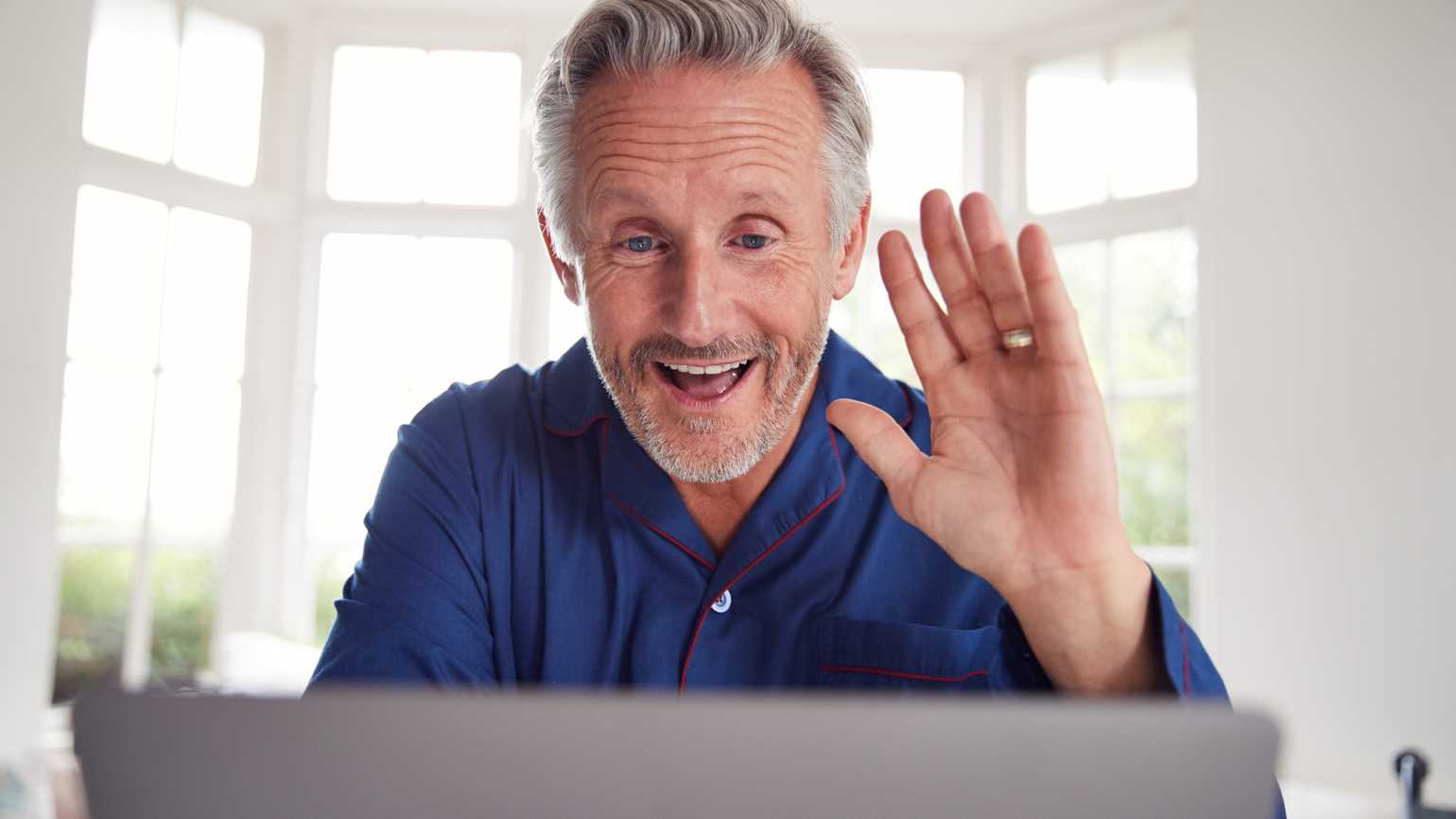 An older gentleman greeting someone on his laptop.