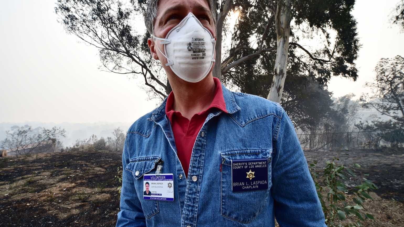 Los Angeles Sheriff's Department chaplain Pastor Brian La Spade walks through properties in the Points Dume neighborhood of Malibu, California, where members of his congregation live, on November 10, 2018, after the Woolsey Fire tore through the neighborhood overnight. - Firefighters in California on Saturday battled raging blazes at both ends of the state that have left at least nine people dead and thousands of homes destroyed, but there was little hope of containing the flames anytime soon. More than 250